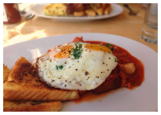 Fried polenta topped with tomato sauce, sausage and eggs